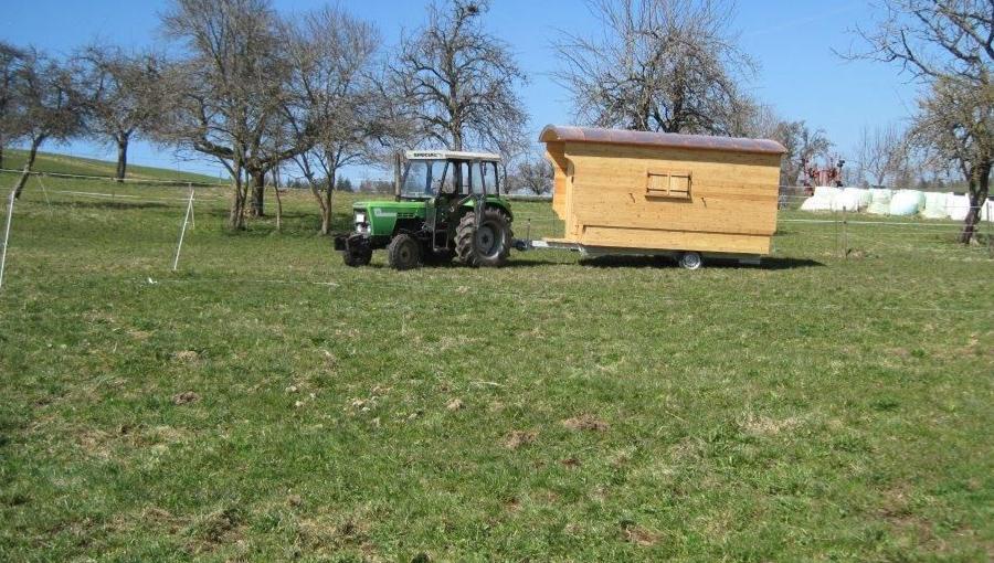 Traktor zieht Schäferwagen auf Bauernhof