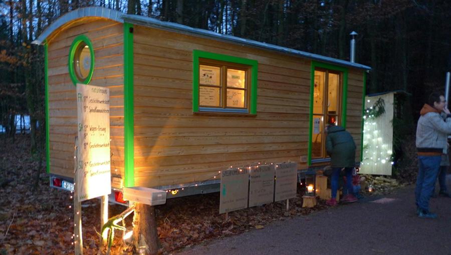 Seminarwagen mit grünen Akzenten und Ofen an einem Weihnachtsmarkt